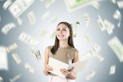 Glückliche Blondine unter einem Dollarregen Stockfoto