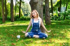 Glückliche Blondine, welche die Natur sitzt auf grünem Gras mit Tasse Kaffee genießen Getrennt auf Schwarzem Stockbilder