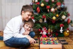 Glückliche Brüder Das Schätzchen und Mutter, die den des Weihnachtsmanns Hut tragen, spielen zusammen Stockbilder