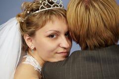 Glückliche Braut auf Schulterbräutigam Stockfotografie