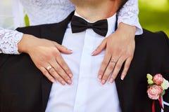 Glückliche Braut, die den Bräutigam mit den Händen umarmt Nahaufnahmeporträt einer Braut und des Bräutigams lizenzfreie stockfotos