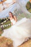 Glückliche Braut, die im Hochzeitskleid wirbelt Stockfoto