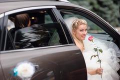 Glückliche Braut in einem Hochzeitsauto Stockbild