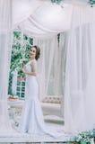Glückliche Braut in einem weißen langen Kleid, mit einer roten Rose in ihrem Haar, Lizenzfreie Stockfotos