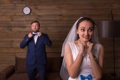 Glückliche Braut gegen den Bräutigam, der am Telefon spricht Lizenzfreie Stockbilder