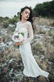 Glückliche Braut im Gebirgshügel auf Sonnenuntergang Lizenzfreie Stockfotografie