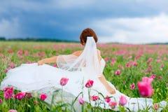 Glückliche Braut im weißen Kleid, das Spaß auf dem Blumenmohnblumengebiet hat stockfotos