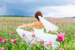 Glückliche Braut im weißen Kleid, das Spaß auf dem Blumenmohnblumengebiet hat stockbild