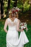 Glückliche Braut mit Blumenstrauß- und Blumenkranz Stockfotos