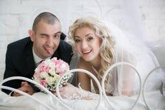 Glückliche Braut mit einem Hochzeitsblumenstrauß von den Rosen und vom netten Bräutigam, der heraus die Zunge setzt Stockbild