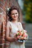 Glückliche Braut mit Hochzeitsblumenstrauß über Backsteinmauer Lizenzfreie Stockbilder