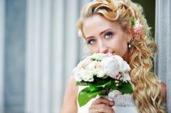 Glückliche Braut mit Hochzeitsblumenstrauß Stockfoto
