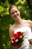 Glückliche Braut mit rotem Blumenstrauß Lizenzfreie Stockfotografie