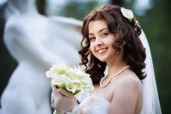 Glückliche Braut mit weißem Hochzeitsblumenstrauß Stockfotos