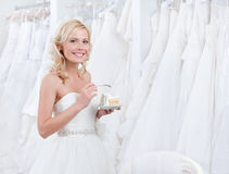 Glückliche Braut schmeckt den Kuchen Stockfoto