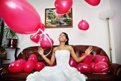 Glückliche Braut spielt mit roten Kugeln Stockbild
