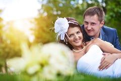 Glückliche Braut und Bräutigam auf dem grünen Gras Lizenzfreies Stockfoto