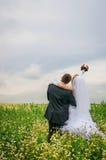 Glückliche Braut und Bräutigam auf einem schönen Feld unter Blumen Stockfoto