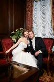Glückliche Braut und Bräutigam in den Luxuxstühlen Stockfotografie