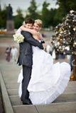 Glückliche Braut und Bräutigam an der Hochzeit gehen auf Brücke lizenzfreies stockbild
