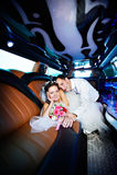 Glückliche Braut und Bräutigam in der Hochzeitslimousine Lizenzfreie Stockfotografie