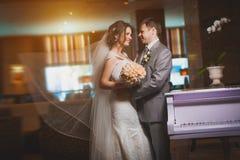 Glückliche Braut und Bräutigam in der modernen Hotelhalle stockfoto