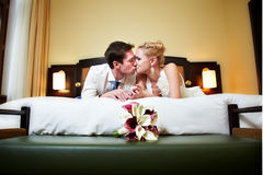 Glückliche Braut und Bräutigam des romantischen Kußes im Schlafzimmer Stockbild