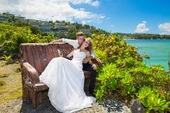 Glückliche Braut und Bräutigam, die auf der Bank vor schönem sitzt Lizenzfreie Stockfotos