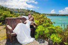 Glückliche Braut und Bräutigam, die auf der Bank vor schönem sitzt Lizenzfreies Stockfoto