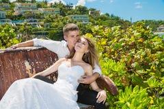 Glückliche Braut und Bräutigam, die auf der Bank vor schönem sitzt Stockbild