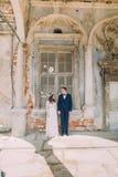 Glückliche Braut und Bräutigam, die einander stehend in einem alten ruinierten Ziegelsteinfenster des alten Gebäudes betrachtet Lizenzfreie Stockfotos