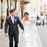 Glückliche Braut und Bräutigam, die in eine alte Stadt geht Stockbild