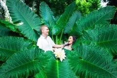 Glückliche Braut und Bräutigam, die Spaß auf einem tropischen Dschungel hat Heiratsa Stockbilder