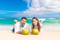 Glückliche Braut und Bräutigam, die Spaß auf einem tropischen Strand mit Kokosnüssen hat Stockbilder