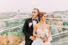 Glückliche Braut und Bräutigam, die weich das Blicken in Richtung auf der Terrasse mit Stadtbildhintergrund umarmt Lizenzfreie Stockfotos