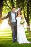 Glückliche Braut und Bräutigam an einem greenl Sommer parken lizenzfreie stockbilder
