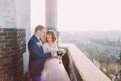 Glückliche Braut und Bräutigam haben einen sinnlichen Moment auf dem Balkon der alten gotischen Kathedrale Stockfotografie