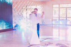 Glückliche Braut und Bräutigam an ihrem ersten Tanz, heiratend im Restaurant mit einer wunderbaren Atmosphäre lizenzfreie stockfotos
