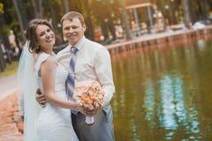 Glückliche Braut und Bräutigam im Park lizenzfreie stockfotografie