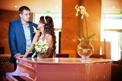 Glückliche Braut und Bräutigam nahe bei dem Klavier Lizenzfreie Stockfotografie