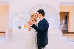 Glückliche Braut und Bräutigam tanzen würdevoll Einige rote Mandeln stockfotos