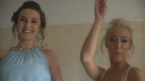 Glückliche Braut und ihre zwei reizend Brautjungfern feiern die Hochzeit und springen auf das Bett stock video