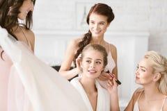 Glückliche Brautjungfern, die der Braut helfen, fertig zu werden Lizenzfreies Stockfoto