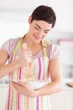Glückliche Brunettefrau, die einen Kuchen vorbereitet Stockbild