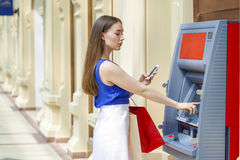 Glückliche Brunettefrau, die Geld von der Kreditkarte an ATM zurücknimmt Lizenzfreies Stockfoto