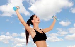 Glückliche Brunettefrau, die ihre Muskeln tont stockfotografie
