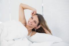 Glückliche Brunettefrau, die in ihrem Bett aufwacht stockbild