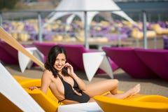 Glückliche Brunettefrau mit einem perfekten Körper in einem schwarzen Badeanzug, der auf einem gelben Ruhesessel auf dem Luxus-Re stockbild