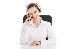Glückliche Call-Center-Frau, die am Schreibtisch sitzt Lizenzfreie Stockfotografie