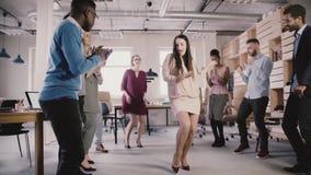 Glückliche CEO-Geschäftsfrau, die Unternehmensleistung mit einem Tanz an der zufälligen multiethnischen Büroparteizeitlupe feiert stock footage